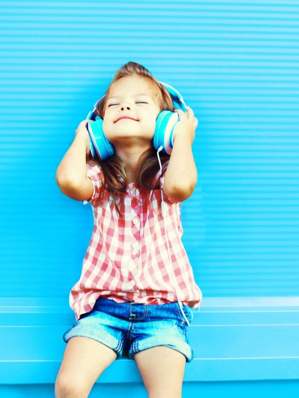 81777994 - happy little girl child listens to music in headphones on a colorful blue background